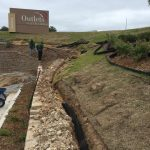 Our landscaping crew installing a 250ft French Drain at the Outlets of Little Rock